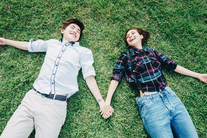 芝生に寝転がる若い男女(欧米人・アジア人)