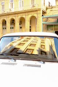 ヴィンテージカーの窓に写ったキューバ・ハバナの街並み