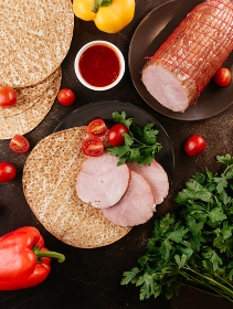 fresh homemade sausage on a dark background with vegetables