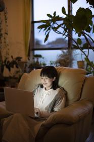 ひかえめな照明の部屋のソファで、ノートパソコンを使う若い女性
