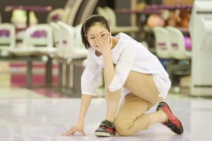ボウリングをして目を覆う女性