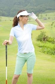 ゴルフクラブを持って遠くを見る女性