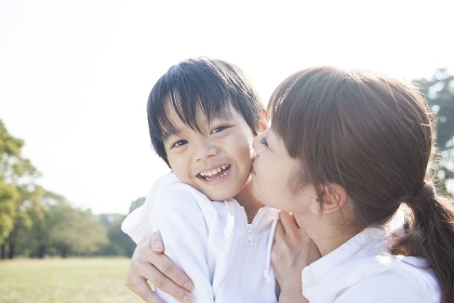 男児の頬にキスする母