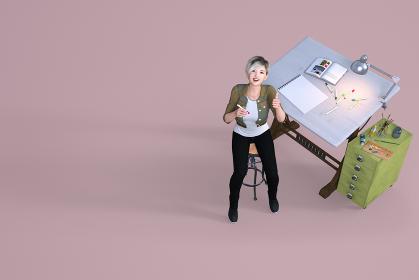 デザイン会社の女性スタッフが笑顔でグッドサインをしながら上を見上げている