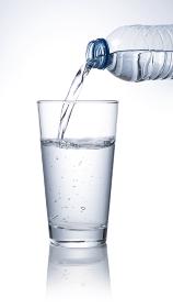 ペットボトルの水をグラスに注ぐ
