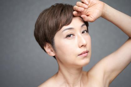 額に手を当てる中年の日本人女性