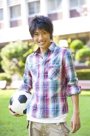 サッカーボールを持って微笑む男子大学生