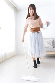 部屋を掃除する若い女性