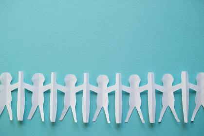 新型コロナ対策で衝立を挟んで繋がる人々の切り紙。青い背景とコピースペース。
