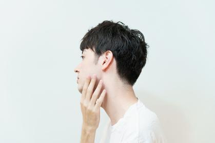 肌の状態を確かめる若い男性