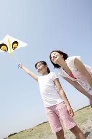 凧を揚げる少女と母親