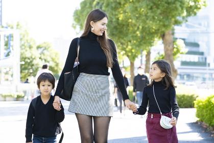 手を繋いで屋外を歩く母親と子供2人