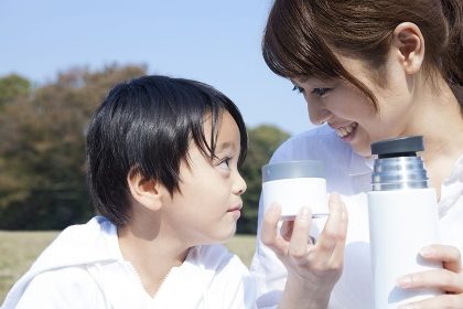 水筒のジュースを飲む母子