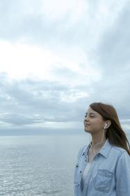 海岸で音楽を聴く笑顔の日本人女性