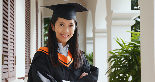 Asian woman wearing graduation gown in university campus