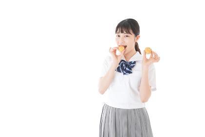 おやつを食べる制服姿の女子学生