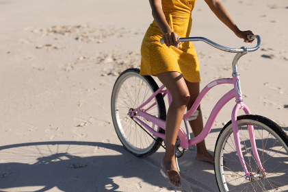 A happy, attractive mixed race woman enjoying free time on beach on a sunny day, wearing a yellow dress, riding a bicycle, sun shining on her. Relaxing summer vacation.