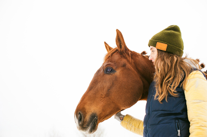 Woman in winter clothes and a horse standing together. love and care for horses. animal portrait on a white background.