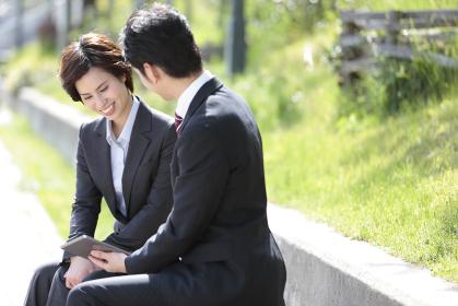 タブレットPCを見るビジネスマンとビジネスウーマン