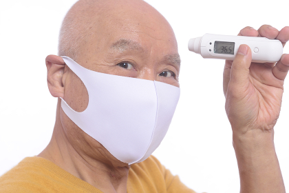 マスクをしているシニア男性が電子体温計で体温測定をしている