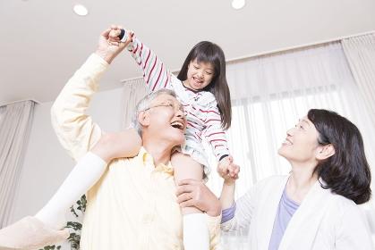 孫を肩車する祖父と笑顔の祖母