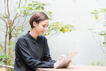 屋外のテラスでタブレット端末を操作する若い女性