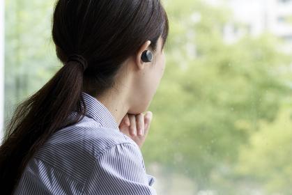 ワイヤレスイヤホンで音楽を聴く若い女性