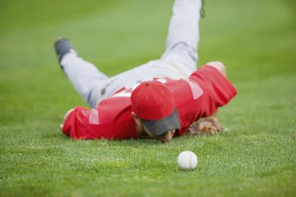 芝の上の野球ボールとユニフォームを着た選手