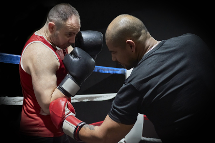 Determined male boxers training in health club in the ring