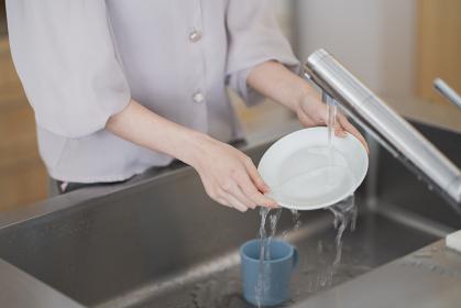 キッチンでお皿を洗う女性