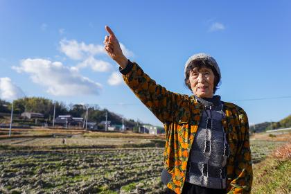 田舎で上を指差す高齢の女性
