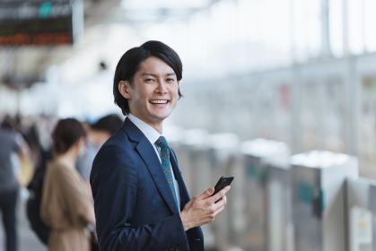 駅のホームでスマートフォンを持つ若い男性・通勤とIoTのイメージ