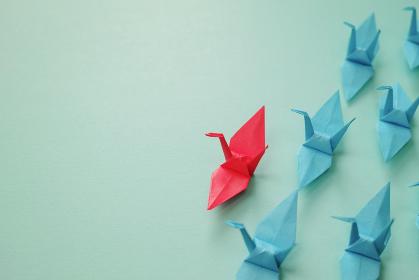 複数の青い折り鶴を率いる一つの赤い折り鶴。左に青緑のコピースペース。