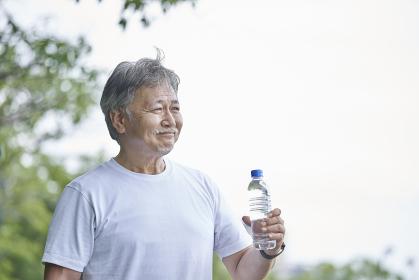 ペットボトルに入った水を持つシニアの男性