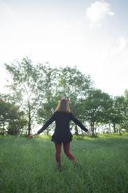 夕暮れの公園に立つハロウィンの仮装をした女性の後ろ姿