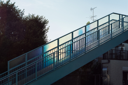 空の光に反射して虹色に光る歩道橋のガラス