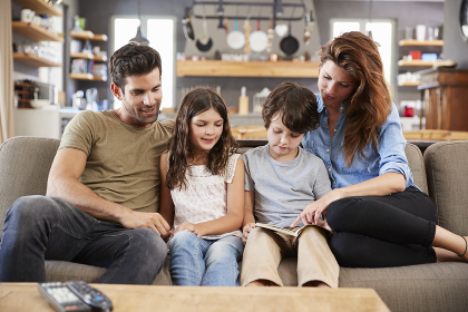 Family Sitting On Sofa In Lounge Reading Book Together