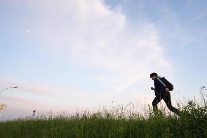 草原を走る男性