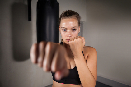 Female boxer practicing boxing in fitness studio