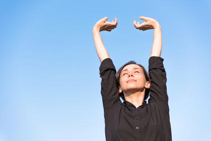 青空の下でリラックスをする若い女性