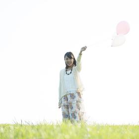 草原で風船を持ち微笑む女性