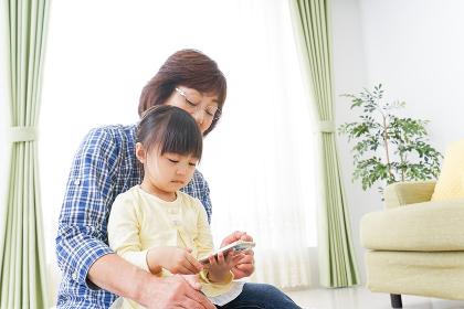 おばあちゃんとスマホを使う子供