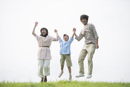 草原でジャンプをする家族