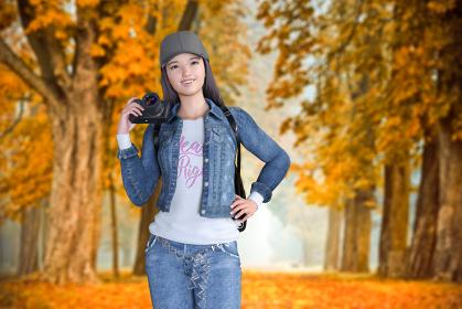 紅葉した街路樹を背景にカメラを持った帽子をかぶった女の子が笑顔でポーズする