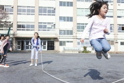 大縄跳びをする小学生と教師
