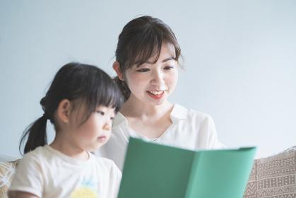 ソファに座って絵本を読む親子
