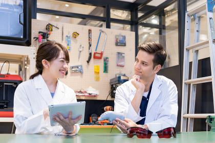実験室で会話をする白衣の研究者