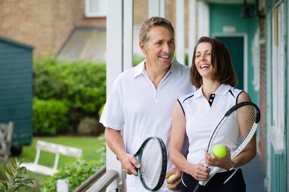 テニスラケットを持つミドル夫婦