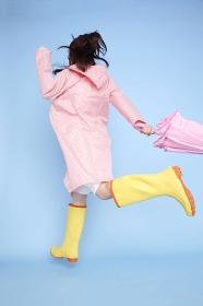 雨具を着てジャンプする女性