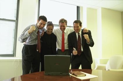 パソコンに向かいガッツポーズをする会社員